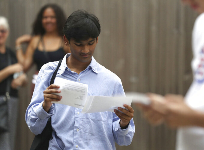 Students at Peter Symonds College, Winchester, England, receive their A-Level results on Thursday Aug. 13, 2020. Thousands of school-leaving children in Britain have been left distraught after finding out Thursday that they were given lower-than-expected grades, with many questioning how the results were calculated after the coronavirus pandemic cancelled exams key for college applications. (Andrew Matthews/PA via AP)