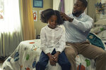 """This image released by Netflix shows Melody Hurd, left, and Kevin Hart in a scene from """"Fatherhood."""" (Philippe Bosse/Netflix via AP)"""