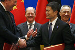 German Finance Minister Olaf Scholz, center, and Chinese Vice Premier Liu He, right, applaud as they witness a signing ceremony after the China-Germany High Level Financial Dialogue at the Diaoyutai State Guesthouse in Beijing, Friday, Jan. 18, 2019. (AP Photo/Andy Wong, Pool)