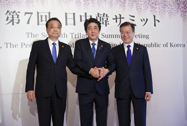 FILE- In this May 9, 2018, file photo, Chinese Premier Li Keqiang, left, Japanese Prime Minister Shinzo Abe, center, and South Korean President Moon Jae-in, right, pose for photographers prior to their summit in Tokyo. The leaders of China, Japan and South Korea are holding a trilateral summit in China this week amid feuds over trade, military maneuverings and historical animosities. Most striking has been a complex dispute between Seoul and Tokyo, while Beijing has recently sought to tone down its disagreements with its two neighbors.(AP Photo/Eugene Hoshiko, File)