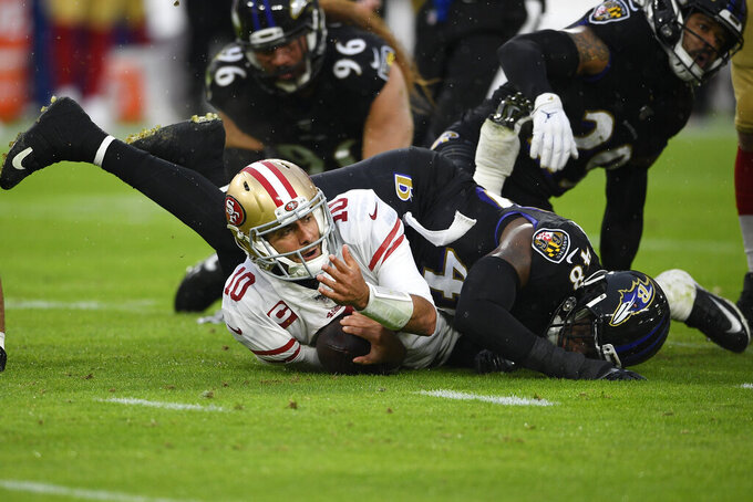 San Francisco 49ers quarterback Jimmy Garoppolo (10) looks up after being tackled by Baltimore Ravens inside linebacker Patrick Onwuasor (48) in the first half of an NFL football game, Sunday, Dec. 1, 2019, in Baltimore, Md. (AP Photo/Nick Wass)