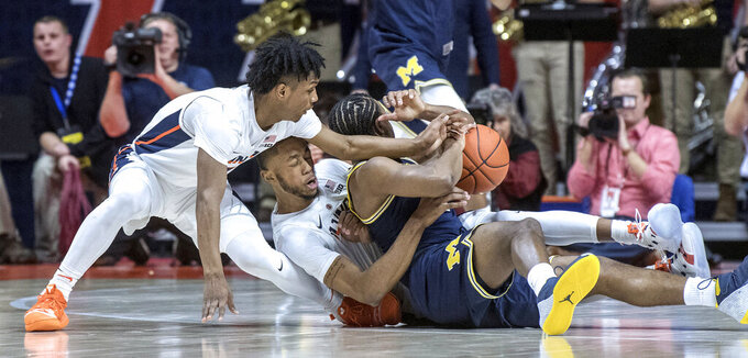 Illinois guards Trent Frazier and Alan Griffin battle for the ball with Michigan guard Zavier Simpson, right, during the first half of an NCAA college basketball game in Champaign, Ill., Thursday, Jan. 10, 2019. (AP Photo/Rick Danzl)