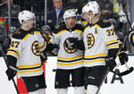 Boston Bruins celebrate after center Brad Marchand, center, scored against the Vegas Golden Knights during the first period of an NHL hockey game Tuesday, Oct. 8, 2019, in Las Vegas. (AP Photo/John Locher)