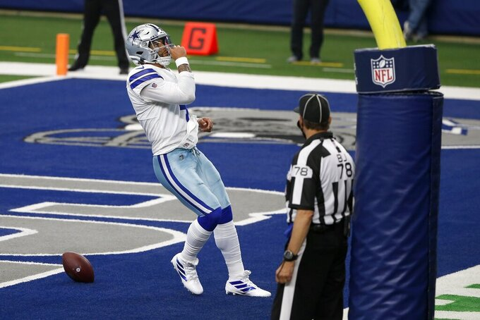 Dallas Cowboys quarterback Dak Prescott (4) celebrates running the ball for a touchdown as back judge Greg Meyer (78) looks on in the second half of an NFL football game against the Atlanta Falcons in Arlington, Texas, Sunday, Sept. 20, 2020. (AP Photo/Ron Jenkins)