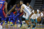 Charlotte Hornets' Devonte' Graham, far right, gathers up a loose ball as teammate Caleb Martin, middle, holds off Detroit Pistons' Langston Galloway during the first half of an NBA preseason basketball game in Charlotte, N.C., Wednesday, Oct. 16, 2019. (AP Photo/Bob Leverone)