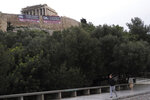 A woman walks as members of Greece's Communist Party stand on the ancient Acropolis Hill over giant banners protesting against the Prespa Agreement in front of the ancient Parthenon temple, in Athens, on Thursday, Jan. 24, 2019. Greek lawmakers are debating a historic agreement aimed at normalizing relations with Macedonia in a stormy parliamentary session scheduled to culminate in a Thursday vote, while opponents have announced a series of protests. (AP Photo/Petros Giannakouris)