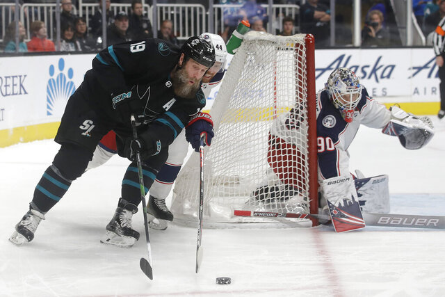 San Jose Sharks center Joe Thornton (19) skates with the puck against Columbus Blue Jackets defenseman Vladislav Gavrikov (44) and goaltender Elvis Merzlikins (90) during the first period of an NHL hockey game in San Jose, Calif., Thursday, Jan. 9, 2020. (AP Photo/Jeff Chiu)