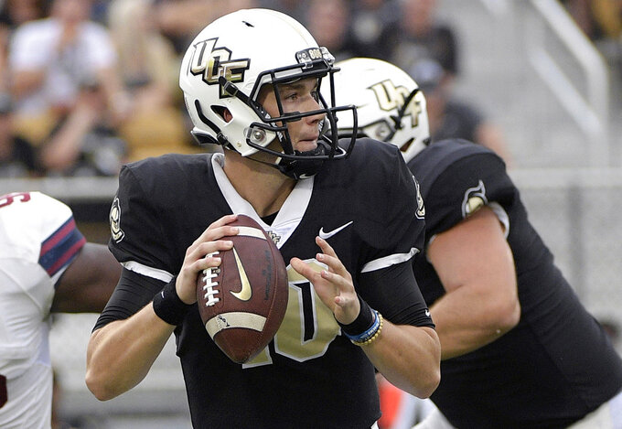 FILE - In this Sept. 8, 2018, file photo, Central Florida quarterback McKenzie Milton (10) throws a pass during the first half of an NCAA college football game against South Carolina State in Orlando, Fla. No. 10 Central Florida plays at Memphis on Saturday. These two teams played a classic shootout last year, with UCF edging Memphis 62-55 in double overtime to win the American Athletic Conference championship game during its unbeaten season. (AP Photo/Phelan M. Ebenhack, File)