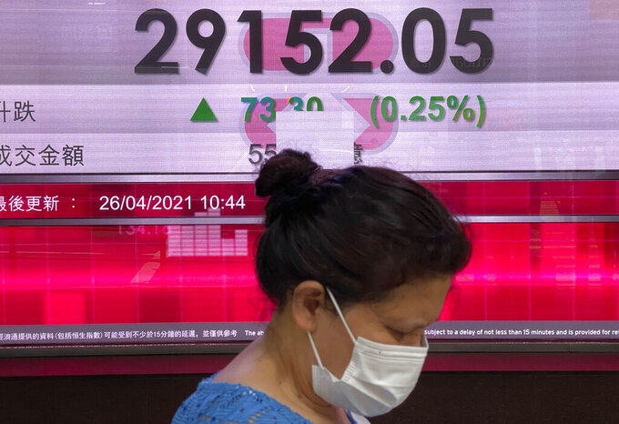 A woman wearing a face mask walks past a bank's electronic board showing the Hong Kong share index at Hong Kong Stock Exchange in Hong Kong Monday, April 26, 2021. (AP Photo/Vincent Yu)