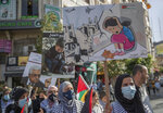 """Palestinian women carry posters that read """"no for terrorizing the children, Gaza, Palestine,"""" during a protest supporting the children in Gaza, in the West Bank city of Ramallah, Thursday, May 20, 2021. (AP Photo/Nasser Nasser)"""