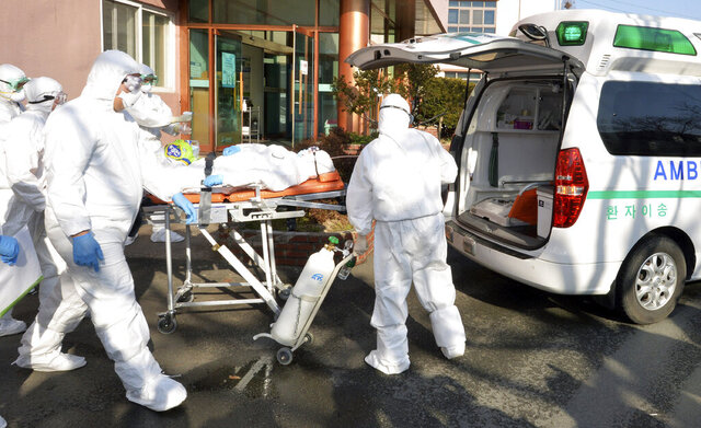 Medical workers wearing protective gears carry a patient suspected of contracting the new coronavirus toward an ambulance at Daenam Hospital in Cheongdo, South Korea, Friday, Feb. 21, 2020. South Korea reported 100 new virus cases Friday, bringing the country's total to 204, many of them clustered around a southeastern city, and raising fears that the outbreak is getting out of control. (Lee Moo-ryul/Newsis via AP)
