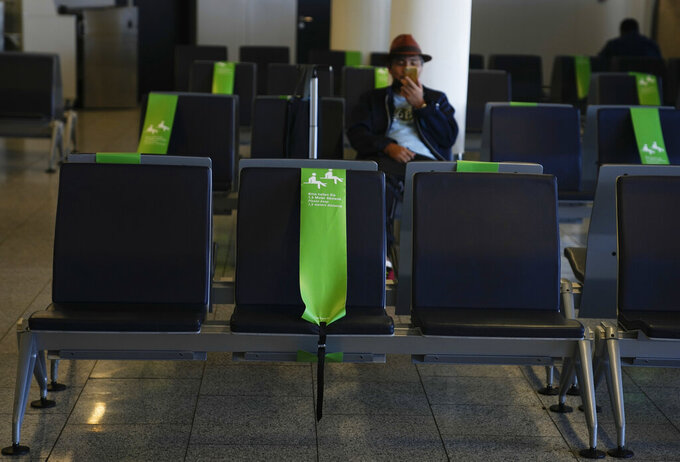 A passenger looks at his phone in Frankfurt, Germany on Sunday, July 18, 2021. (AP Photo/Natacha Pisarenko)