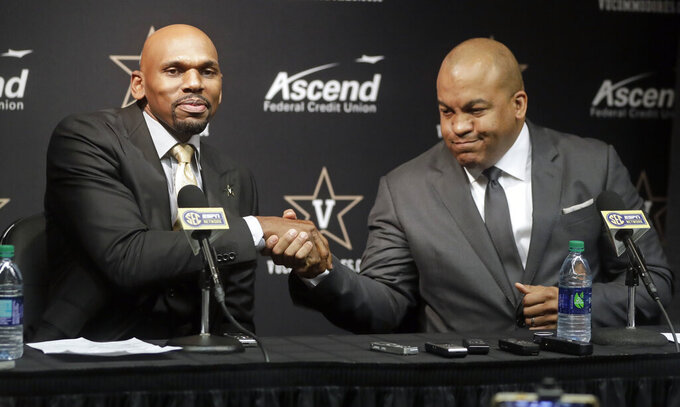Vanderbilt basketball coach Jerry Stackhouse, left, is introduced by Athletics Director Malcom Turner during a news conference Monday, April 8, 2019, in Nashville, Tenn. Stackhouse was hired to replace Bryce Drew as head coach. (AP Photo/Mark Humphrey)
