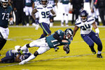 Philadelphia Eagles' Carson Wentz (11) is tackled by Seattle Seahawks' Quandre Diggs (37) during the first half of an NFL football game, Monday, Nov. 30, 2020, in Philadelphia. (AP Photo/Chris Szagola)