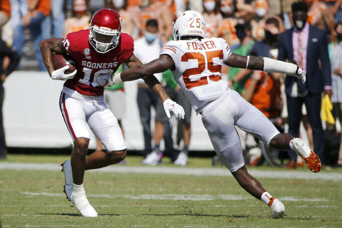 Oklahoma wide receiver Theo Wease (10) evades a tackle by Texas defensive back B.J. Foster (25) during an NCAA college football game in Dallas, Saturday, Oct. 10, 2020. (AP Photo/Michael Ainsworth)