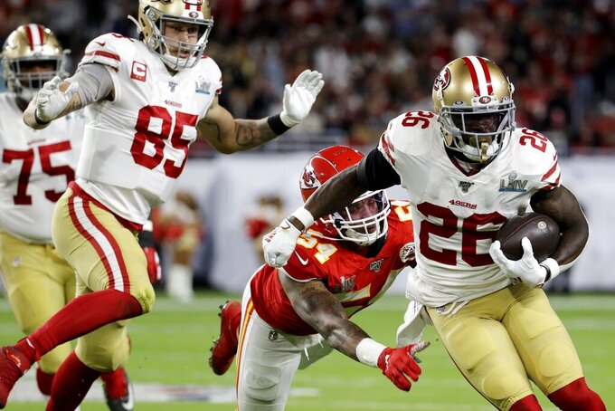 San Francisco 49ers' Tevin Coleman (26) runs against Kansas City Chiefs' Damien Wilson (54) during the first half of the NFL Super Bowl 54 football game Sunday, Feb. 2, 2020, in Miami Gardens, Fla. (AP Photo/Patrick Semansky)