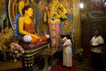 In this Nov. 15, 2019, photo, Sri Lankan Buddhists pray inside a temple in Colombo, Sri Lanka. About 70% of the 22 million people in this island nation off India's southern coast are Buddhists, mainly ethnic Sinhalese. Hindus, mainly ethnic Tamils, make up 12.6% of the population, while another 9.7% are Muslim and 7.6% are Christian. Buddhist nationalists are rejoicing the election of the country's newest leader. They hope he ushers in another golden era for the nation's ethnic majority. (AP Photo/Dar Yasin)