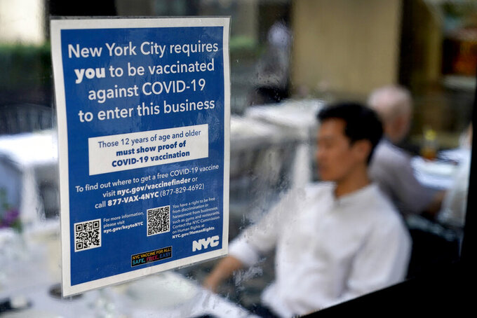 FILE - In this Sept. 13, 2021, file photo, a notice explaining that proof of vaccination is required to dine inside is seen at a restaurant in midtown Manhattan in New York. In both the U.S. and the EU, officials are struggling with the same question: how to boost vaccination rates to the max and end a pandemic that has repeatedly thwarted efforts to control it. In the United States, President Joe Biden has issued sweeping vaccine mandates. (AP Photo/Seth Wenig, File)