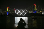 A photographer takes pictures of the illuminated Olympic rings in front of the Rainbow Bridge Friday, Jan. 24, 2020, in the Odaiba district of Tokyo. Tokyo put on a flashy fireworks display on Friday to mark the 6-months-to-go milestone for this summer's Olympics. (AP Photo/Jae C. Hong)