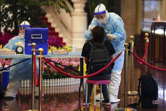 A medical worker takes a swab from a foreign reporter who was selected to cover the opening ceremony of the Chinese People's Political Consultative Conference (CPPCC) for the coronavirus test, at a hotel in Beijing, Thursday, May 21, 2020. China is strictly limiting the number of journalists who can cover its ongoing legislative session because of the coronavirus outbreak.  (AP Photo/Andy Wong)