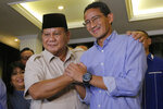 Losing presidential candidate Prabowo Subianto, left, shakes hands with his running mate Sandiaga Uno during a press conference in Jakarta, Indonesia, Thursday, June 27, 2019. Indonesia's top court ruled Thursday against the former special forces general's challenge to the country's election results that alleged massive and systematic fraud, paving the way for incumbent Joko Widodo's second term as president. (AP Photo/Tatan Syuflana)