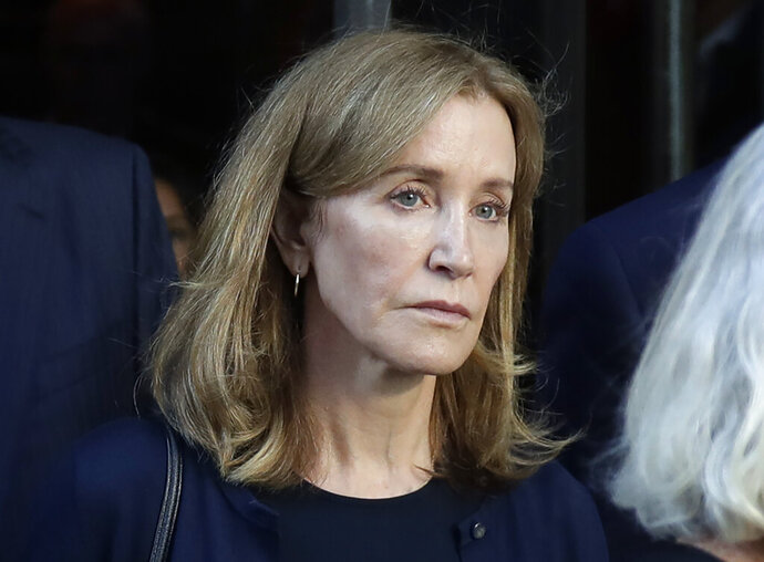 FILE - This Sept. 13, 2019 file photo shows actress Felicity Huffman leaving federal court after her sentencing in a nationwide college admissions bribery scandal in Boston. A representative for Huffman says she reported to a federal prison in California to serve a two-week sentence on Tuesday, Oct. 15. Last month a federal judge in Boston sentenced Huffman to 14 days in prison, a $30,000 fine, 250 hours of community service and a year's probation after she pleaded guilty to fraud conspiracy for paying an admissions consultant $15,000 to have a proctor correct her daughter's SAT answers. (AP Photo/Elise Amendola, File)