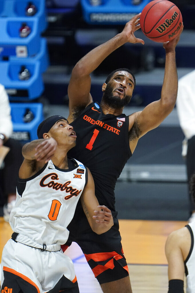Oregon State forward Maurice Calloo (1) pulls down a rebound over Oklahoma State guard Avery Anderson III (0) during the first half of a men's college basketball game in the second round of the NCAA tournament at Hinkle Fieldhouse in Indianapolis, Sunday, March 21, 2021. (AP Photo/Paul Sancya)