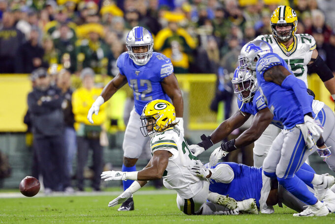 Green Bay Packers running back Aaron Jones (33) fumbles the ball during the first half of an NFL football game against the Detroit Lions, Monday, Oct. 14, 2019, in Green Bay, Wis. (AP Photo/Jeffrey Phelps)