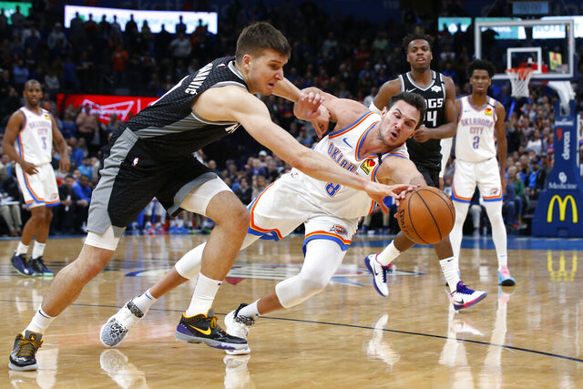 Oklahoma City Thunder forward Danilo Gallinari (8) and Sacramento Kings guard Bogdan Bogdanovic, left, reach for the ball during the second half of an NBA basketball game Thursday, Feb. 27, 2020, in Oklahoma City. (AP Photo/Sue Ogrocki)