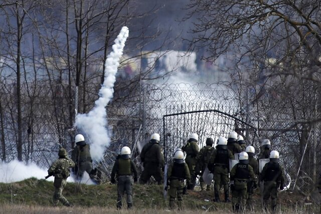 Greek police guard as migrants gather at a border fence on the Turkish side, during clashes at the Greek-Turkish border in Kastanies, Evros region, on Saturday, March 7, 2020. Thousands of refugees and other migrants have been trying to get into EU member Greece in the past week after Turkey declared that its previously guarded borders with Europe were open. (AP Photo/Giannis Papanikos)
