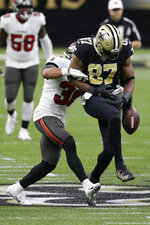 New Orleans Saints tight end Jared Cook (87) fumbles the ball as he is hit by Tampa Bay Buccaneers strong safety Antoine Winfield Jr., left, during the second half of an NFL divisional round playoff football game, Sunday, Jan. 17, 2021, in New Orleans. The Buccaneers' Devin White recovered the ball. (AP Photo/Butch Dill)