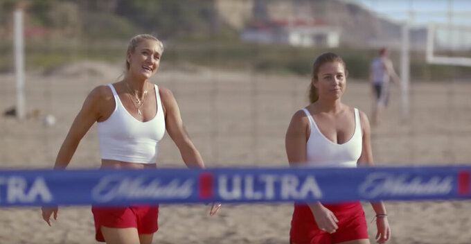 This undated image provided by Michelob ULTRA shows Kerri Walsh Jennings, left, and Brooke Sweat in a scene from the company's 2020 Super Bowl NFL football spot. Michelob Ultra stresses its low calories and low carbs in an ad that shows talk show host Jimmy Fallon and wrestler John Cena working out. (Michelob ULTRA via AP)