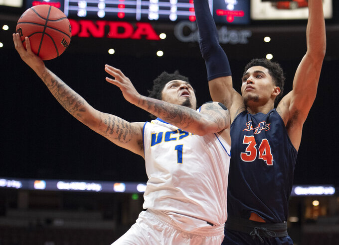 UC Santa Barbara guard Ar'Mond Davis, left, goes up for a basket under as Cal State Fullerton forward Jackson Rowe defends during the first half of an NCAA college basketball game at the Big West men's tournament in Anaheim, Calif., Friday, March 15, 2019. (AP Photo/Kyusung Gong)