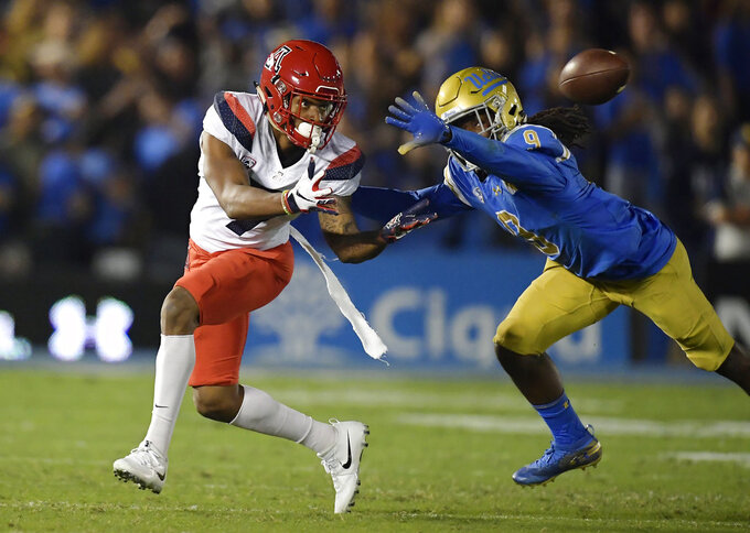 Arizona wide receiver Devaughn Cooper, left, attempts a catch as UCLA defensive back Elijah Gates knocks it down during the first half of an NCAA college football game Saturday, Oct. 20, 2018, in Pasadena, Calif. (AP Photo/Mark J. Terrill)