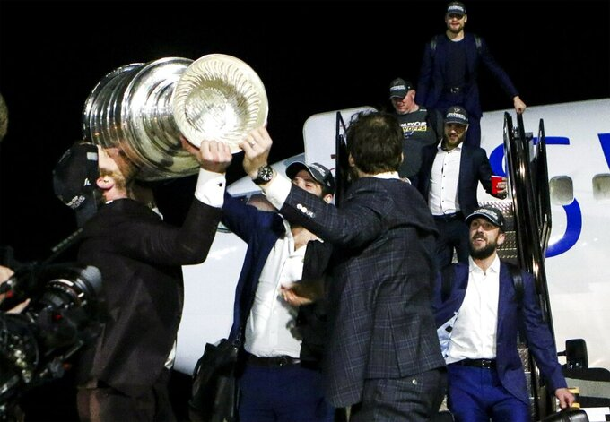 St. Louis Blues NHL hockey player Jaden Schwartz kisses the Stanley Cup as the Blues arrive at the airport in St. Louis early Thursday, June 13, 2019. The Blues defeated the Boston Bruins 4-1 in Game 7 of the Stanley Cup finals to win their first NHL championship Wednesday night in Boston. (Colter Peterson/St. Louis Post-Dispatch via AP)