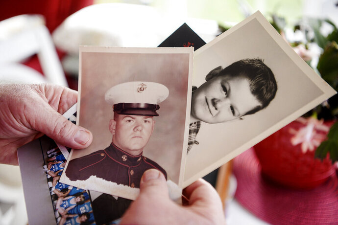 This photo taken April, 18, 2019, shows Stephen Henderson, a Marine Corps combat veteran of the Vietnam War, holding photos of himself, at his home in Fairview, N.C. Henderson was one of 38 original participants of the Creative Writing Program at Charles George VA Medical Hospital in East Asheville, which helped Vietnam War veterans cope with their past and present traumas.  (Angela Wilhelm/The Asheville Citizen-Times via AP)