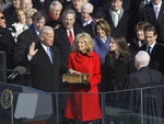 """FILE - In this Tuesday, Jan. 20, 2009 file photo, Vice President-elect Joe Biden takes the oath of office from Justice John Paul Stevens as his wife, Jill Biden, holds the Bible at the U.S. Capitol in Washington. While many presidents have used Bibles for their inaugurations, the Constitution does not require the use of a specific text and specifies only the wording of president's oath. That wording also doesn't include the phrase """"so help me God,"""" but every modern president has appended it to their oaths and most have chosen symbolically resonant Bibles for their inaugurations. (AP Photo/Elise Amendola)"""