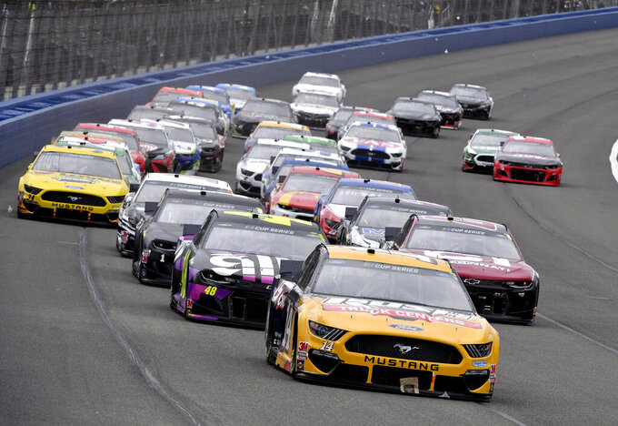 Pole sitter Clint Bowyer (14) leads Jimmie Johnson (48) and the rest of the field toward Turn 1 to start a NASCAR Cup Series auto race Sunday, March 1, 2020 in Fontana, Calif. (AP Photo/Will Lester)