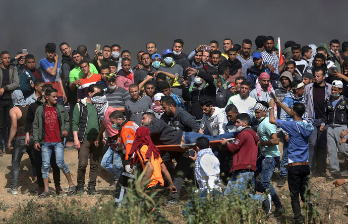 FILE - In this April 6, 2018 photo, Palestinian protesters carry a wounded man during a protest at the Gaza Strip's border with Israel. Israel said Monday April 16, 2018, that it is sanctioning the owners of Gaza buses used to transport Hamas activists to border demonstrations. The head of Cogat, the military body for Palestinian civilian affairs, wrote on Facebook that 14 companies ignored warnings and bused