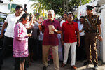 Sri Lanka's former Defense Secretary and presidential candidate Gotabaya Rajapaksa, center, waves to the media as he arrives to cast vote with his wife Ayoma, left, out side a polling center in Embuldeniya, on the outskirts of Colombo, Sri Lanka, Saturday, Nov. 16, 2019. Polls opened in Sri Lanka's presidential election Saturday after weeks of campaigning that largely focused on national security and religious extremism in the backdrop of the deadly Islamic State-inspired suicide bomb attacks on Easter Sunday. (AP Photo/Eranga Jayawardena)