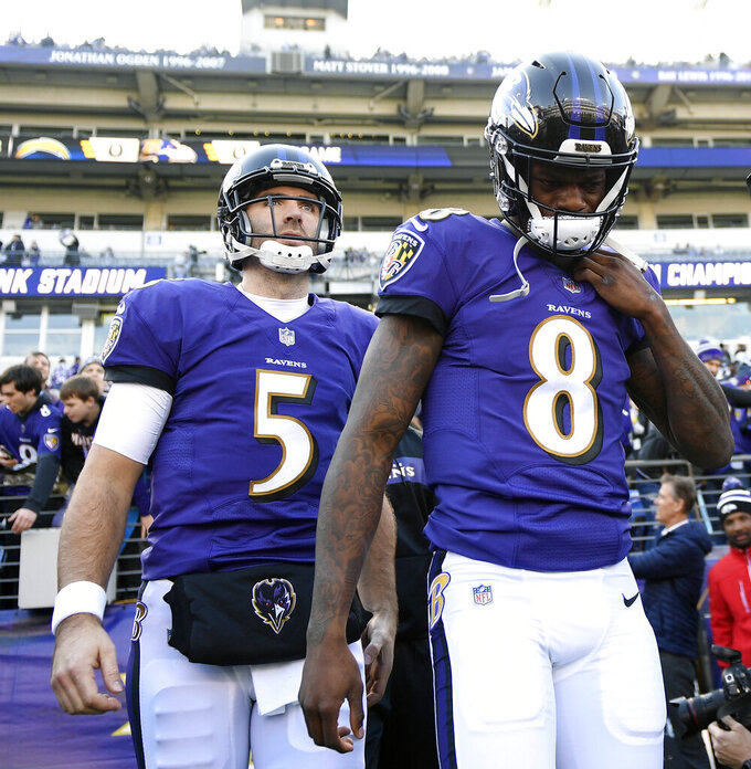 FILE - In this Jan. 6, 2019, file photo, Baltimore Ravens quarterbacks Lamar Jackson (8) and Joe Flacco walk onto the field before an NFL wild card playoff football game against the Los Angeles Chargers, in Baltimore. A person with knowledge of the trade tells The Associated Press, Wednesday, Feb. 13, 2019, that the Denver Broncos have agreed to acquire Baltimore Ravens quarterback Joe Flacco in exchange for a fourth-round pick in this year's NFL draft. The person spoke on condition of anonymity because neither team announced the deal. Flacco became expendable in Baltimore with the emergence of rookie Lamar Jackson. (AP Photo/Nick Wass, File)