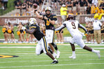 Missouri quarterback Connor Bazelak, center, throws a pass to teammate Tyler Badie, left, past Central Michigan defensive lineman Thomas Incoom, right, during the first half of an NCAA college football game Saturday, Sept. 4, 2021, in Columbia, Mo. (AP Photo/L.G. Patterson)