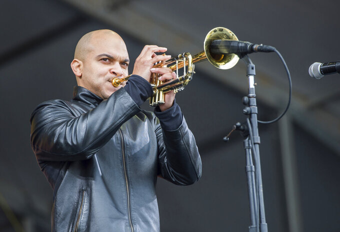 FILE - In this May 4, 2017 file photo, Irvin Mayfield performs at the New Orleans Jazz and Heritage Festival in New Orleans. Mayfield and his musical partner, pianist Ronald Markham, each pleaded guilty Tuesday, Nov. 10, 2020, to a conspiracy to commit fraud charge. The federal charge stemmed from the time the two spent as board members of the charitable New Orleans Public Library Foundation. Prosecutors alleged that they steered more than $1.3 million raised for public libraries to themselves by funneling it through the New Orleans Jazz Orchestra, which Mayfield founded. (Photo by Amy Harris/Invision/AP, File)
