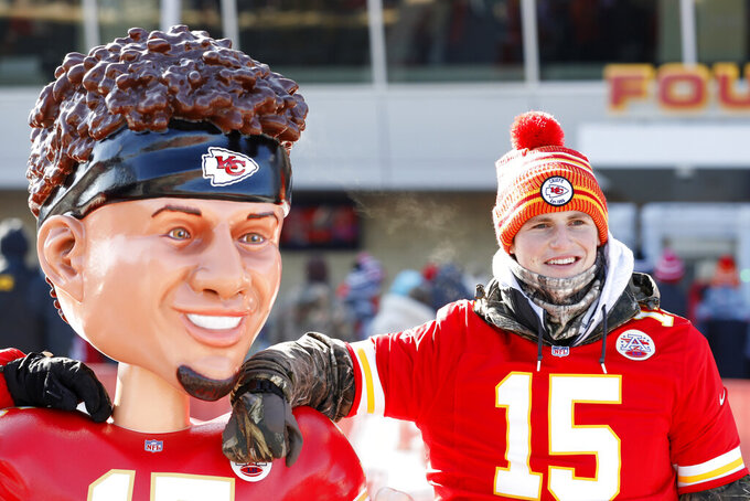 A Kansas City Chiefs fan has a picture taken with a bobble head of Kansas City Chiefs quarterback Patrick Mahomes outside Arrowhead Stadium before the NFL AFC Championship football game against the Tennessee Titans Sunday, Jan. 19, 2020, in Kansas City, MO. (AP Photo/Charlie Neibergall)