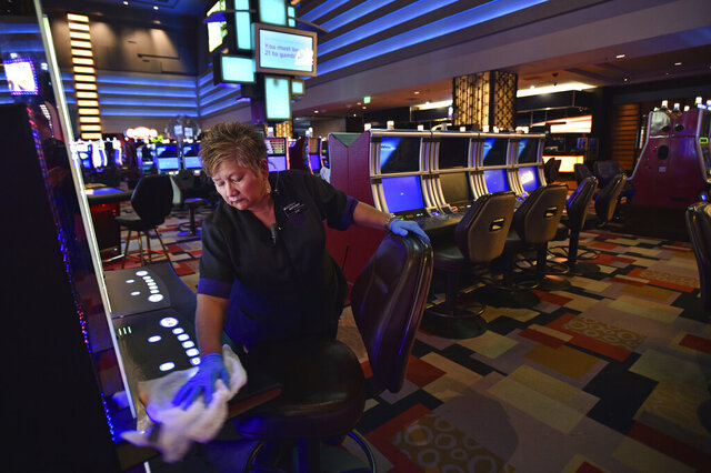 Antonia Garcia cleans slot machines inside the Planet Hollywood hotel-casino after all casinos in the state were ordered to shut down due to the coronavirus Wednesday, March 18, 2020, in Las Vegas. For most people, the new coronavirus causes only mild or moderate symptoms, such as fever and cough. For some, especially older adults and people with existing health problems, it can cause more severe illness, including pneumonia.(AP Photo/David Becker)