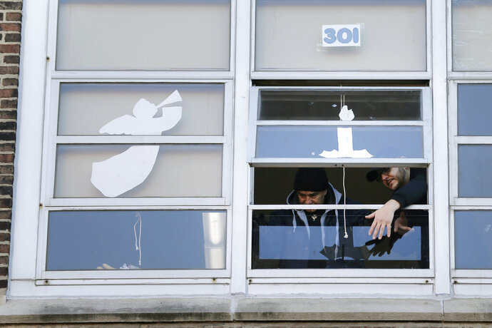 Workmen replace a window that was broken by gunfire at the Sacred Heart school in Jersey City, N.J., Thursday, Dec. 12, 2019. Investigators are looking to pinpoint what prompted a deadly attack on a Jewish market in Jersey City amid fears that it was motivated by anti-Semitism, as the nearby school reopened Thursday. (AP Photo/Seth Wenig)