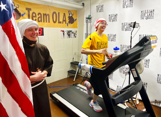 In this Aug. 23, 2020 photo, Sister Stephanie Baliga, right, runs a marathon on a treadmill in the basement of the Mission of Our Lady of the Angels church in Chicago. When the Chicago Marathon was canceled this year due to the coronavirus pandemic, Sister Baliga and her fellow nuns livestreamed the run and raised money for their community. (PJ Weiland via AP)