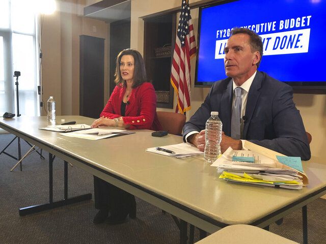 Gov. Gretchen Whitmer, left, briefs the media as state budget director Chris Kolb looks on during Whitmer's budget proposal in the Romney Building, on Thursday, Feb. 6, 2020, in Lansing, Mich. Whitmer says her plan focuses on education, health care and the environment. (AP Photo/David Eggert)