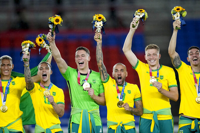 Players of Brazil celebrate with the medals after defeating Spain in the men's soccer final match at the 2020 Summer Olympics, Sunday, Aug. 8, 2021, in Yokohama, Japan. (AP Photo/Andre Penner)