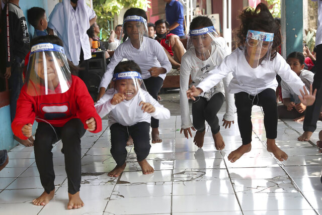 Children wearing masks as a precaution against the coronavirus, take part in a